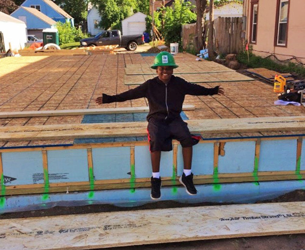 Matthias Jeffrie is photograph in front of what will be he and his mother LaVera Jeffrie's new Habitat for Humanity home in St. Paul, Minneapolis. They moved into their home in 2017.