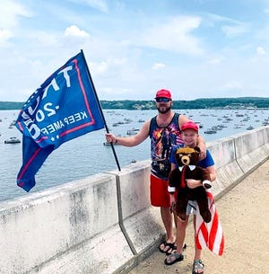 Carl Goss and his daughter, Avery, stand on a highway bridge overlooking the boats assembled Saturday on Norfork Lake for a boat parade to express support for President Trump.