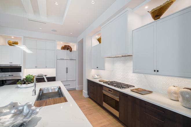 The kitchen features an elevated cabinet combination of milk chocolate-finished maple bases paired with white, beveled edge Shaker-style uppers, sable pulls and knobs, and white Pompeii quartz countertops with light veining