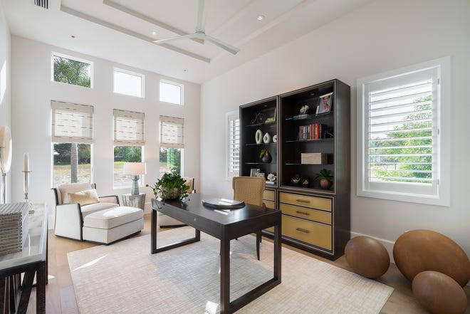The ideal work-from-home headquarters, a handsome, light-filled study features a trio of windows, coffered ceilings, and a nearby half bath.