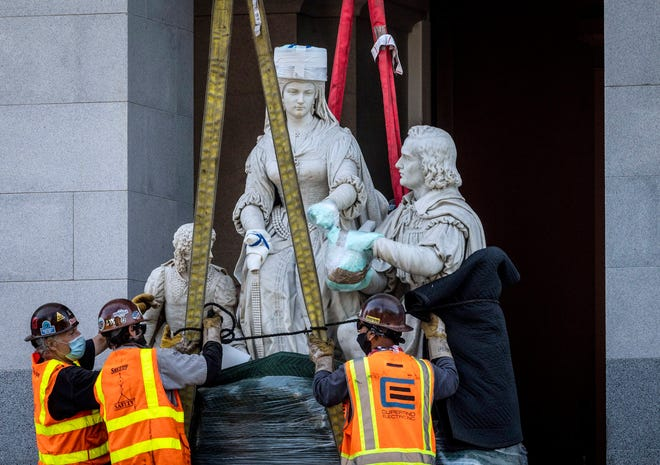 A construction crew moves a 5-ton statue of Christopher Columbus and Queen Isabella to a flatbed truck at the west steps of the Capitol in downtown Sacramento, Calif., Tuesday, July 7, 2020. The statue was removed from the Capitol's rotunda, which was its home since 1883, two weeks after Legislature leaders announced it would come down. (Daniel Kim/The Sacramento Bee via AP)