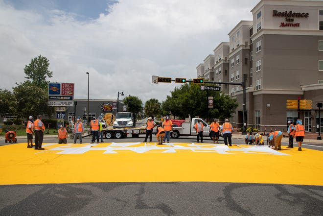 City employees work to lay down the stencil for a Black Lives Matter mural in the intersection of Gaines Street and Railroad Avenue Tuesday, July 7, 2020.