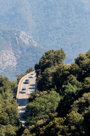 Motorists travel around Amphitheater Point in Sequoia National Park on Monday, July 6, 2020. Smoke from the Crews Fire in Santa Clara County has added to the haze.
