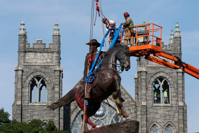 Crews attach straps to the statue Confederate General J.E.B. Stuart on Monument Avenue July 7, 2020, in Richmond, Va. The statue is one of several that will be removed by the city.