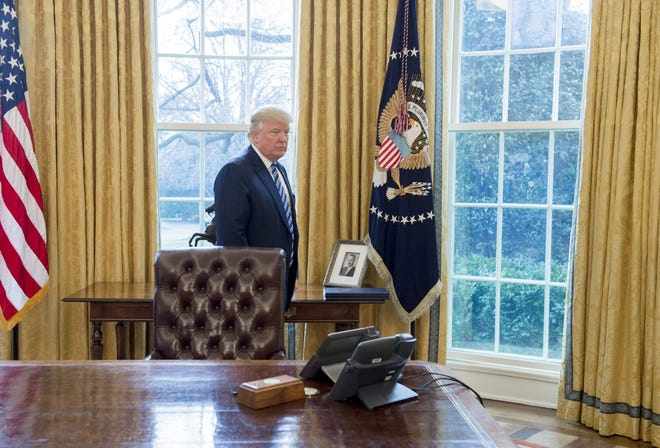 In this photo taken in 2017, a photograph of Fred Trump, the father of US President Donald Trump, is seen in the Oval Office.