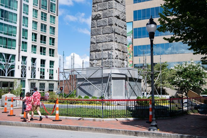 Workers with a city contractor begin putting scaffolding around the Vance Monument in downtown Asheville on July 8, 2020. A shroud will then cover the monument as part of a resolution that calls for the monument's alteration or removal. The Vance Monument honors Zebulon Baird Vance a confederate soldier, war governor and U.S. Senator who died in 1894.