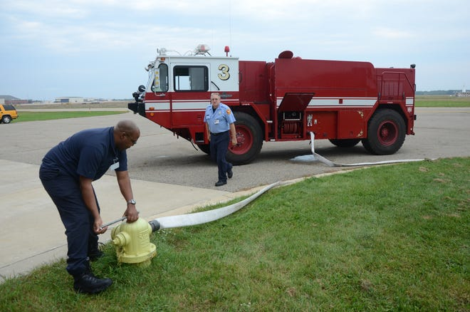 Firefighter Ed Marshall, left, and Lt. Richard Teinert fill a crash truck with water at the airport station in 2014.  Trace Christenson/The Enquirer