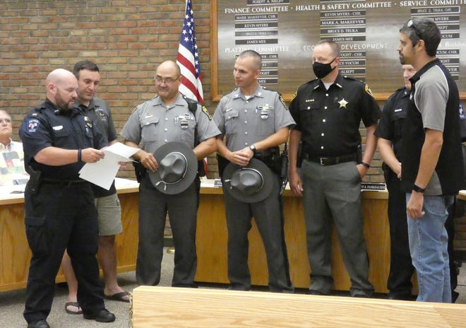 Bucyrus police Lt. Tom Walker , left, holds a signed copy of the city's resolution supporting law enforcement as he stands before council with other representatives of the city's police department, the Ohio Highway Patrol, the Crawford County Sheriff and council President Kurt Fankhauser on Tuesday.