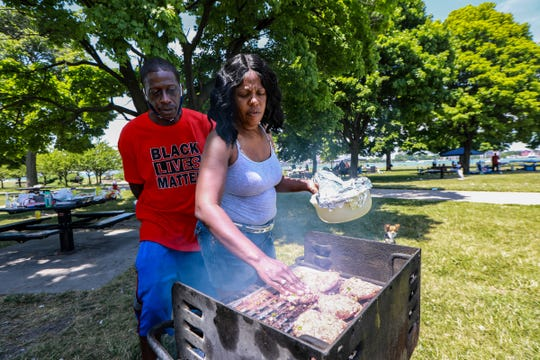 William Page, 53, of Detroit and Lisa Bell, 54, of Highland Park barbecue for the fourth of July together at Belle Isle in Detroit on July 4, 2020. Bell says she knows Page because they went to Highland Park high school together.