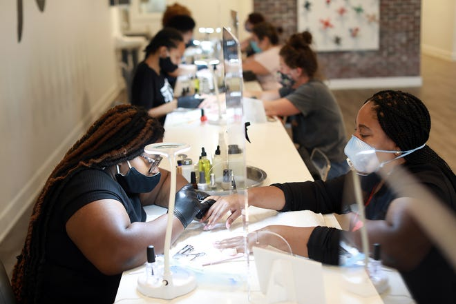 Tatiana Johnson, 22, Roseville gives Blake Grannum, 36, of Detroit a manicure at the Ten Nail bar at the New Center location in Detroit on July 7, 2020. Masks are now required and plexiglass was installed at each station to separate customers from employees.