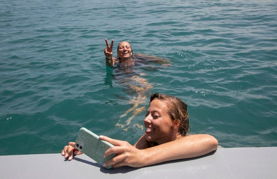 After a day of golfing, Kasey Mackley, 26, of St. Clair takes a selfie with Victoria Szuminski, 24, as they cool off in the St. Clair River off the Palmer Park boardwalk.