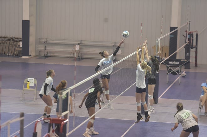 Pryor MacEachran tips the ball over two blockers during Norco Juniors Volleyball Club tryouts for 18-and-under teams Monday, July 6, 2020, at the club's gym in Windsor, Colo.