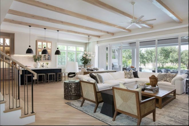The great room of the new Sonoma model at Talis Park has wood beams on the ceiling that match the floor below. A wall of sliding glass doors pocket into the walls to open to the spacious lanai.