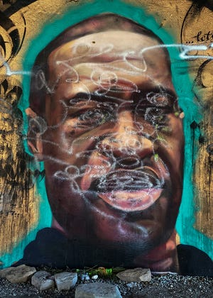 A mural of George Floyd, a Black man killed by a white police officer in Minneapolis, was vandalized on the Lansing River Trail.