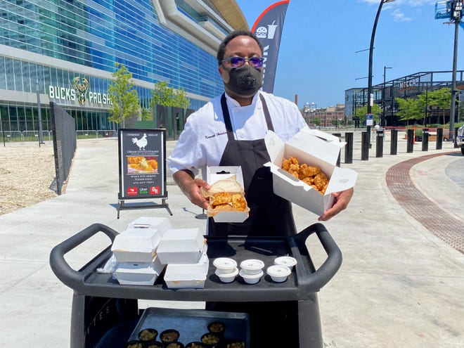Fiserv Forum chef Kenneth Hardiman, appearing at a news conference to introduce Cream City Cluckery, shows some of the restaurant's products