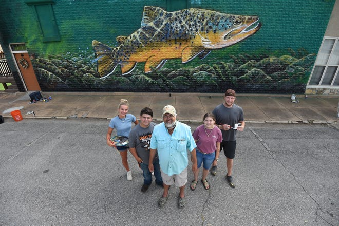 Local artist Duane Hada, front center, is creating a mural in downtown Cotter with help of Ava Obert, far left, Caleb Bailer, second from left, Michael Schraeder, far right and Breanna Hickmott. The mural is being painted on a vacation rental owned by Joey and Vanessa Peglar located at the corner of McLean Avenue and Second Street.