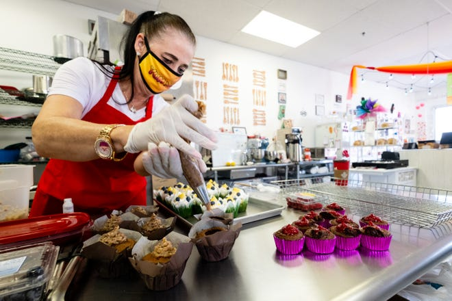 Antoinette McWain, owner of Yum Yums, decorates cupcakes Wednesday, July 8, 2020, in the Marysville eatery.