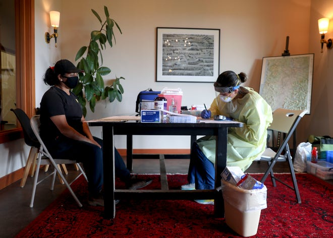 Asuncion Martinez-Vasquez, a farmworker, listens as Erica Sanchez-Lerma reads results from a cholesterol and lipid test at Bethel Heights Vineyard near Salem, Oregon, on Tuesday, July 7, 2020.