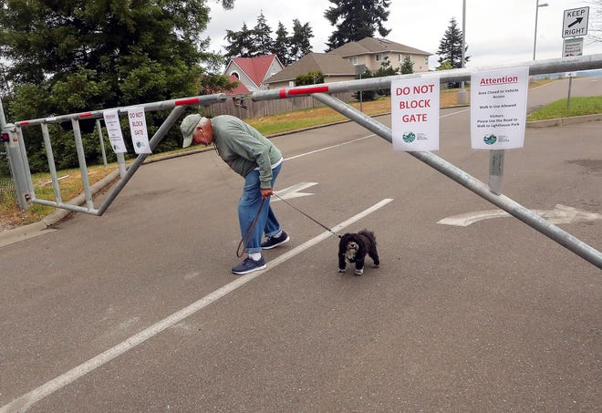 Hansville resident Ed Powers ducks under the closed gate of the Washington Department of Fish and Wildlife's Point No Point water access area after he and dog Murphy made a loop through the area while on their daily walk on Thursday.