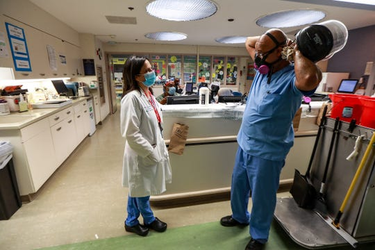 "Dr. Rana Lee Adawi Awdish, M.D., F.C.C.P.  catches up with Intensive Care Nurse Asmerom ""Sammy"" Haile, after he exits a makeshift pod taking off his personal protection equipment in the Medical Intensive Care pod 1 at Henry Ford Hospital in Detroit on June 26, 2020."