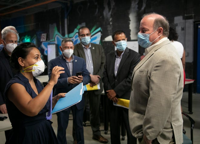 City council member Raquel Castaneda-Lopez speaks to Mayor Mike Duggan before the City of Detroit announces a $750,000 grant from Open Society to help undocumented immigrants affected by Covid-19. The press conference was held at the Detroit Hispanic Development Corporation on July 9, 2020.