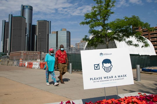Walkers downtown don masks as they walk the Detroit Riverfront on July 9, 2020.