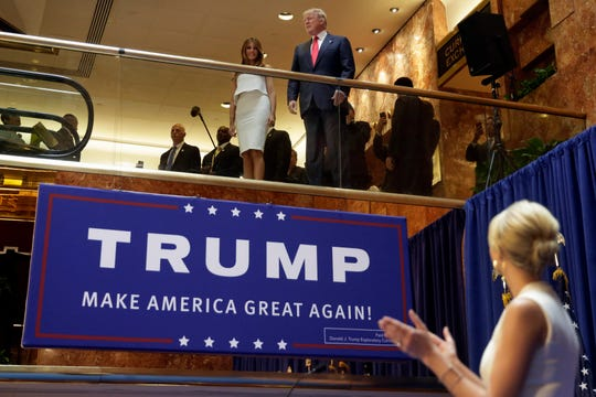 Developer Donald Trump, accompanied by his wife Melania Trump, is applauded by his daughter Ivanka Trump, right as he's introduced before his announcement that he will run for president of the U.S., on June 16, 2015, in the lobby of Trump Tower in New York.