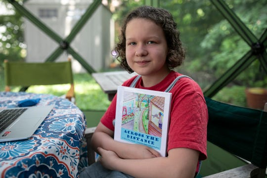 "Genevieve Grunow, 11, poses with the book ""Across The Distance"" on July 7, 2020, that she and her Japhet School classmates wrote together."