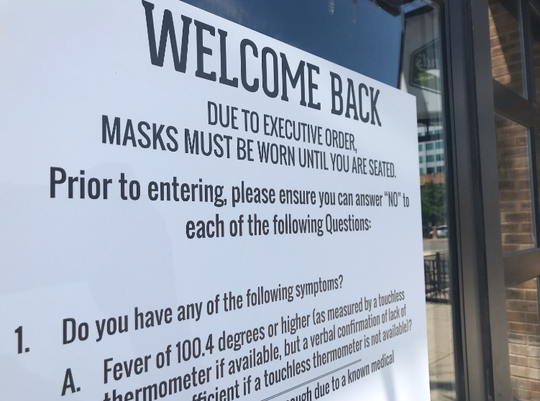 A sign at a restaurant in downtown Lansing near the Michigan Capitol tells people to wear masks until they are seated on Thursday, July 9, 2020.