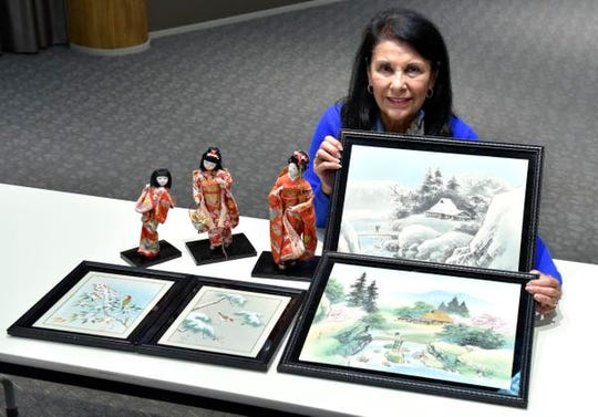 Carole Rizzo-Baum with four silk screen prints from Japan and three porcelain geisha dolls .