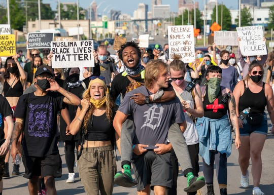 Activists Brendan Scorpio and Jah-T Headd (top) march together with demonstrators down Fort Street and through southwest Detroit, July 1, 2020, to protest police brutality after a Detroit police vehicle drove through a crowd of protesters earlier in the week.