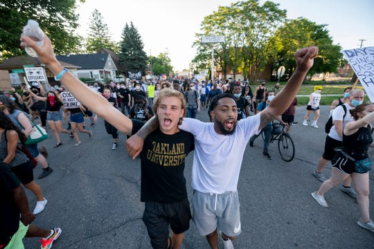 Activists Brendan Scorpio, left, and Dwayne Taylor march together with hundreds of demonstrators through southwest Detroit, June 29, 2020,