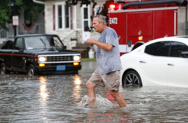 A man makes his way through flood waters Thursday, July 9, 2020, on Park Avenue in Fond du Lac, Wis. A large amount of rain in a short period of time caused streets to flood throughout the city of Fond du Lac.