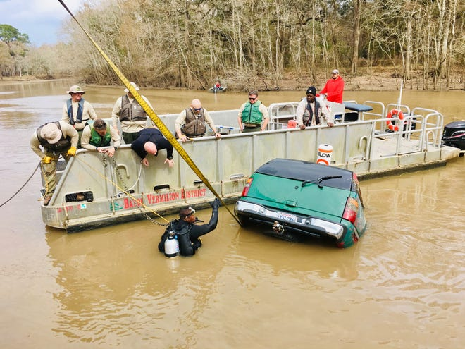 The Lafayette Parish Sheriff's Office's Search and Rescue team works to recover an SUV from the Vermilion River.