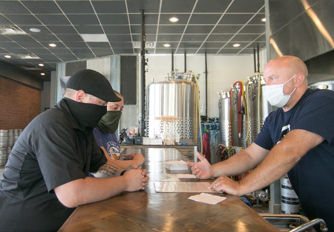 Wearing recommended masks, Hans Olligschlager and Erin Prahl of White Lake listen to brew offerings from Hartland Brewing Company owner Ryan McDonald at the Hartland brewery Thursday, July 9, 2020.
