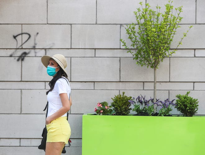 A woman wears a mask in downtown Louisville on Thursday, shortly before Gov. Andy Beshear announced that masks would become mandatory in public on Friday at 5 p.m.
