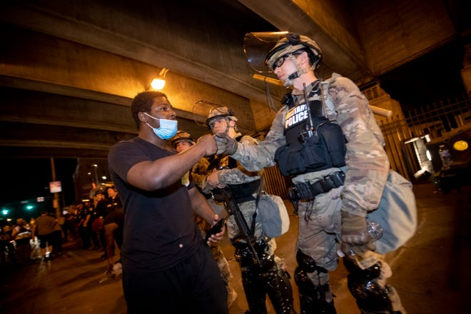 A protestor fist bumps a member of the national guard Tuesday, June 2, 2020, in Louisville.