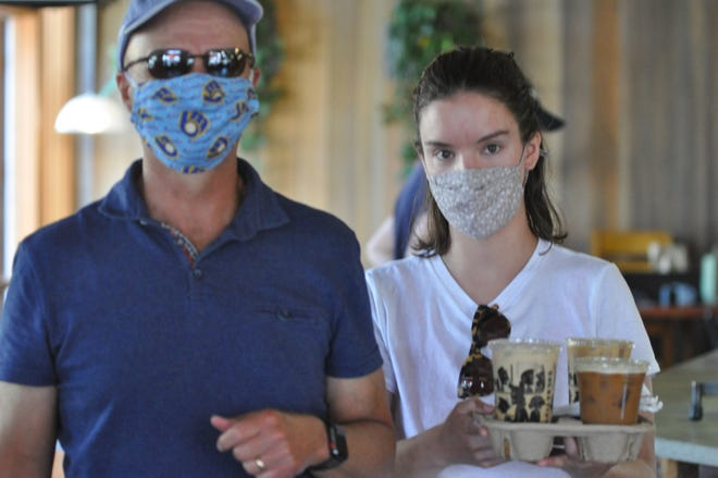 Marty Gagne, left, and his daughter, Clare Gagne, pick up coffee from Colectivo in Shorewood July 9. Colectivo requires masks in its cafes, and soon, the village of Shorewood will require masks in all indoor spaces.