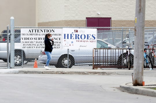 "An American Foods Group employee walks past a sign that says ""Heroes trabajan aquí,"" meaning ""Heroes work here,"" on April 28 in Green Bay."