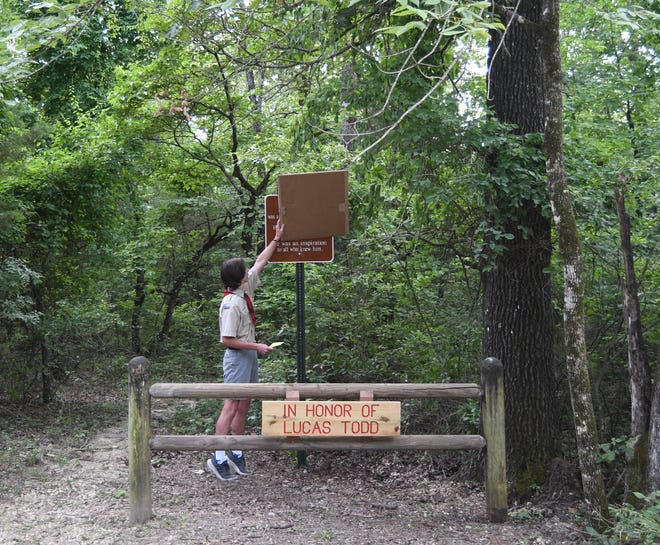 Lucas Sutton unveils a sign donated and installed by the Baxter County Road and Bridge Department in honor of Lucas Todd on Monday, July 6 at the tail head of the George's Cove hiking trail.