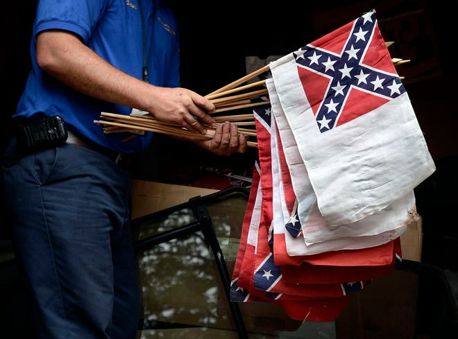 """In this file photo, a cemetery caretaker holds a bundle of banners that includes the second national flag of the Confederacy, the """"Stainless Banner,"""" in Elmira, N.Y. While the Confederate battle flag with its blue X design is the best known flag of the Confederacy, the nation had multiple other flags."""