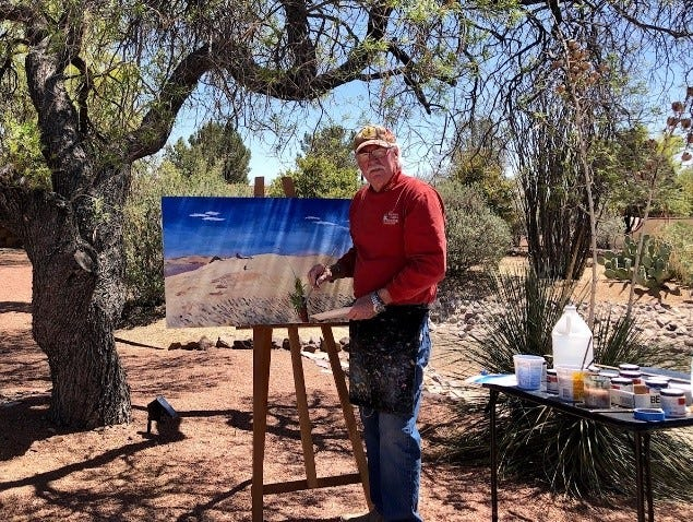 Las Cruces artist Paul Maxwell paints a painting in front of his home.