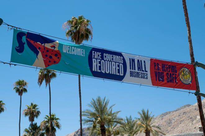 A banner for mandatory face masks during the coronavirus pandemic in Palm Springs, Calif. hangs across North Palm Canyon Drive on Thursday, July 9, 2020.
