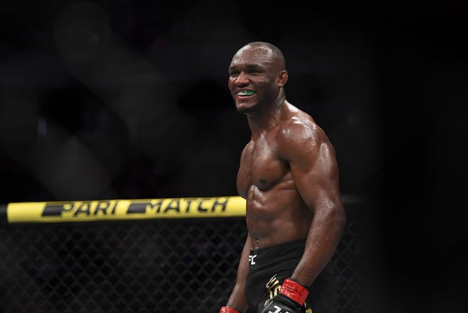 Kamaru Usman (red gloves) reacts after defeating Colby Covington (not pictured) during UFC 245 at T-Mobile Arena.