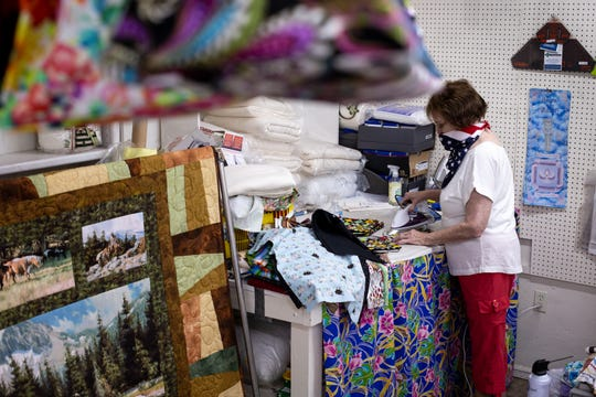 Julie Reiman presses face masks, June 30, 2020, in her shop, Julie's Quilt Shop, in Miami, Arizona. The shop can't keep up with the demand for masks.