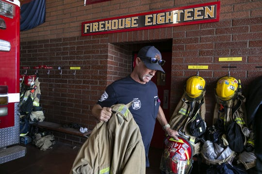 Captain Mike Adelman prepares his turnout gear at Phoenix Fire Station No. 18 in Phoenix on June 30, 2020. The station has had several more calls a day related to COVID-19 since the start of the outbreak.