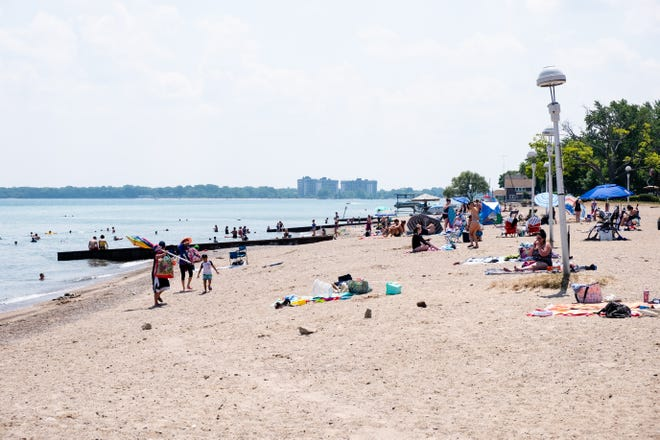 Groups of people hang out at Lakeside Beach Thursday, July 9, 2020, in Port Huron. Despite the coronavirus pandemic, parking pass sales show that the beaches have seen an increase in the number of people going to them over last year.