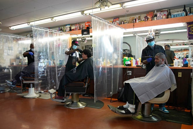 "FILE - In this May 9, 2020, file photo, plastic sheets separate customers at ""A Cut Above the Rest"" barber shop,"