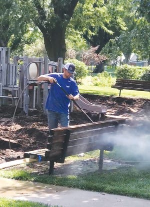 Chad Johnson power washes park benches at St. John's Brown Memorial Park, part of a park beautification effort planned by the St. John City Council.