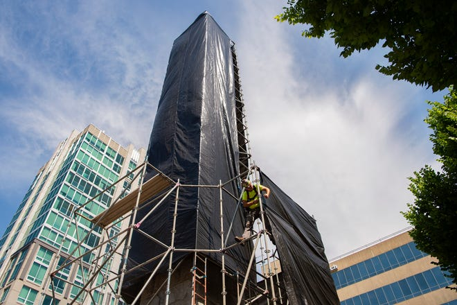 Workers with a city contractor secure a shroud around the Vance Monument in downtown Asheville on July 10, 2020. A Vance Monument Task Force is being formed to decide the future of the monument.